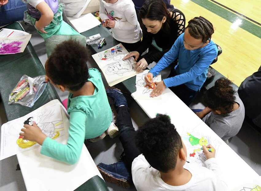 From clockwise, Sage forward Chris Kidd's wife, Chrysti Kidd, Josiah Kidd, 9, Corinthia Kidd, 4, Hezekiah Kidd, 7, and Christin Kidd, 6, color with markers during a game against St. John Fisher Saturday, Feb. 2, 2019 at Sage's Kahl Gymnasium in Albany, NY. (Phoebe Sheehan/Times Union)