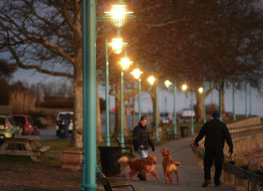 Walkers and their dogs enjoy an evening stroll beneath the new lighting at St. Mary's-by-the-Sea in the Black Rock section of Bridgeport, Conn. on Monday, January 14, 2019. Some 10 of the lights are not watertight and are filling up. Photo: Brian A. Pounds / Hearst Connecticut Media / Connecticut Post