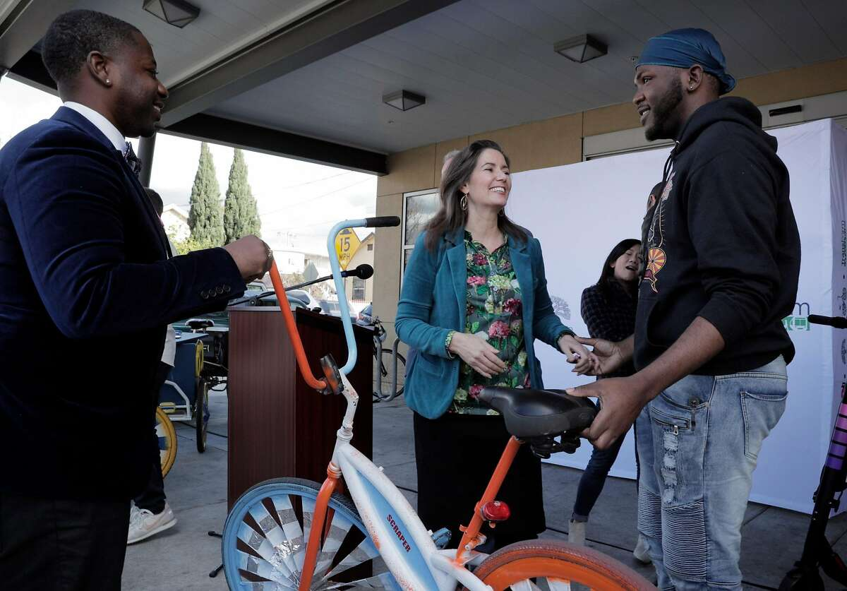 Oakland Mayor Libby Schaaf, center, talks with Champ Stevenson, left, and La'Roy Fitch, right, of the Scraper Bike Team at the 81st Avenue Public Library in Oakland, Calif., on Monday, February 11, 2019. The City of Oakland announced a public/private partnership with Lyft and Scraper Bike Team to sponsor a bike rental station at the library in East Oakland which has long been considered a public transit desert.