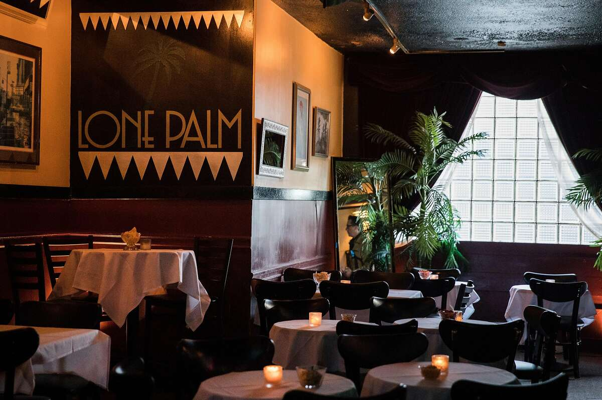 Palm trees and white cloth tables are seen illuminated by a large window in the front of Lone Palm in San Francisco, Calif. Saturday, Jan. 12, 2019.