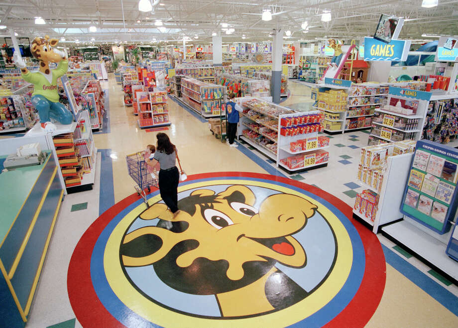 FILE- In this July 30, 1996, file photo, a woman pushes a shopping cart over a graphic of Toys R Us mascot Geoffrey the giraffe at the Toys R Us store in Raritan, N.J. Richard Barry, a former Toys R Us executive and now CEO of the new company called Tru Kids Inc., is exploring freestanding stores, shops within existing stores as well as e-commerce. Tru Kids, owned by former investors of Toys R Us, will manage the Toys R Us, Babies R Us and Geoffrey brands.s. (AP Photo/Daniel Hulshizer, File) Photo: Daniel Hulshizer / Copyright 2018 The Associated Press. All rights reserved.