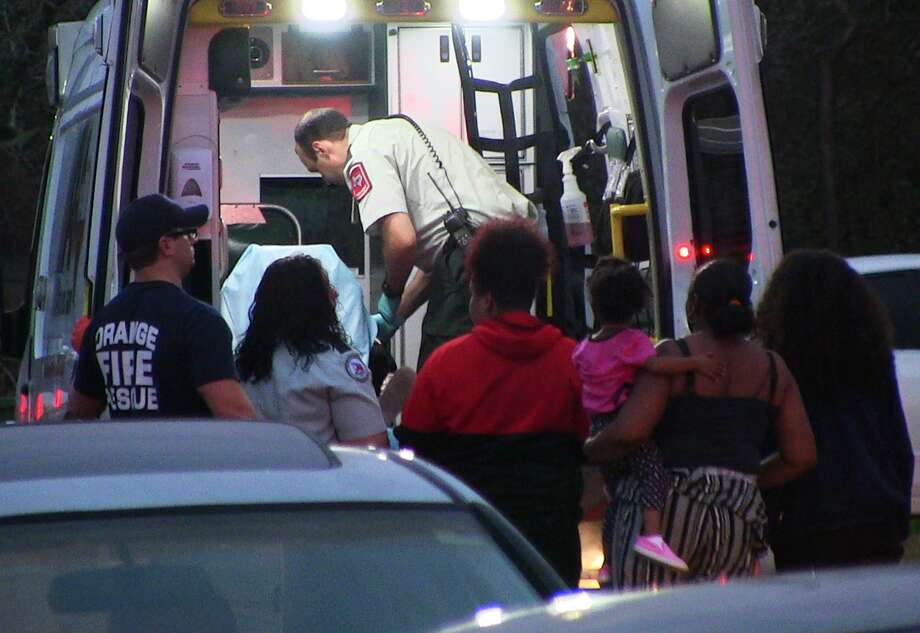 Emergency officials tend to a gunshot child in the back of an ambulance in Orange late Monday evening.