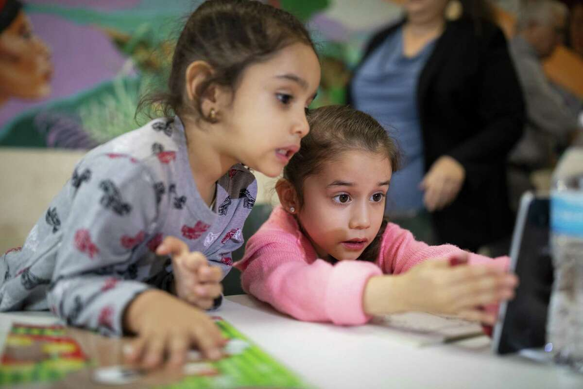 Sisters Michelle and Victoria watch cartoons before a press conference Annunciation House Monday, February 11, 2019, in El Paso, TX. The two sisters were separated from their mother after entering the U.S. illegally and were recently reunited. Photo by Ivan Pierre Aguirre for the San Antonio Express-News