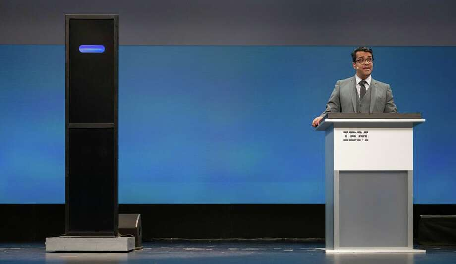 Champion debater Harish Natarajan argues against IBM Debater, represented by a screen with a blue oval, in a competition at the IBM Think conference. Photo: Stephen Shankland/CNET