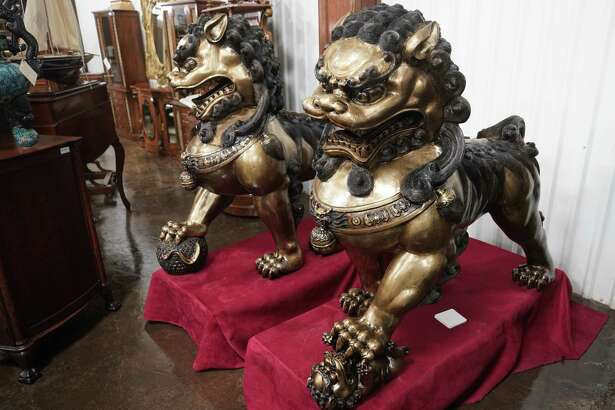 A pair of bronze foo dogs are part of the many items from the Harrison's Fine Antiques & Art store that will be auctioned on Feb. 16 at Gallery Auctions, 13310 Luthe Rd., shown Wednesday, Jan. 30, 2019, in Houston. The male has his paw upon a ball representing the world and the female is restraining a playful cub representing nurture.