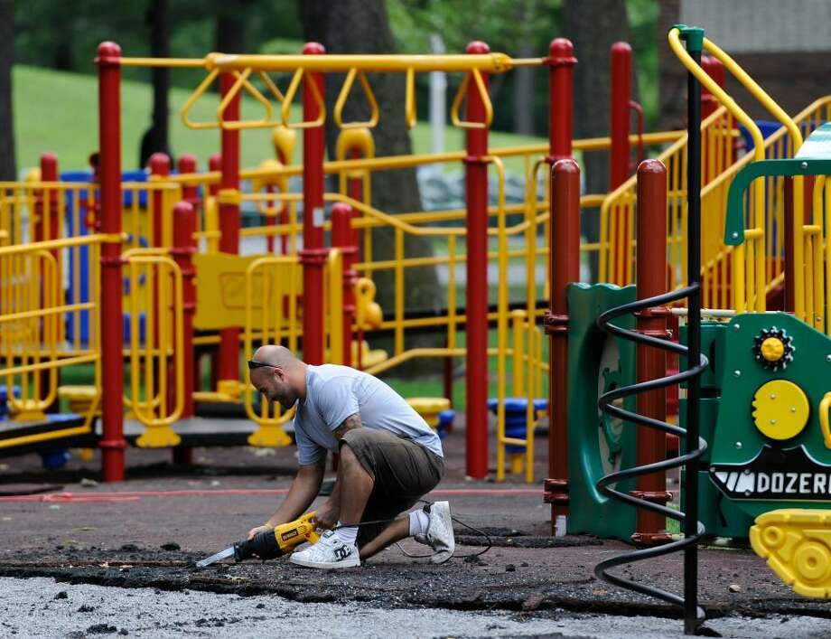 Nick Biondo of Playscape Systems of Cleveland cuts the old ground cover from the Tiny Tots playground in Central Park in Schenectady on July 22, 2010. ( Skip Dickstein / Times Union ) Photo: Skip Dickstein / 2008