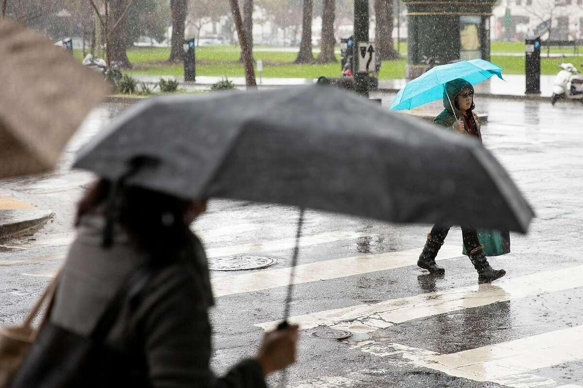 People make their way through the rain on Saturday, Feb. 9, 2019, in San Francisco, Calif.