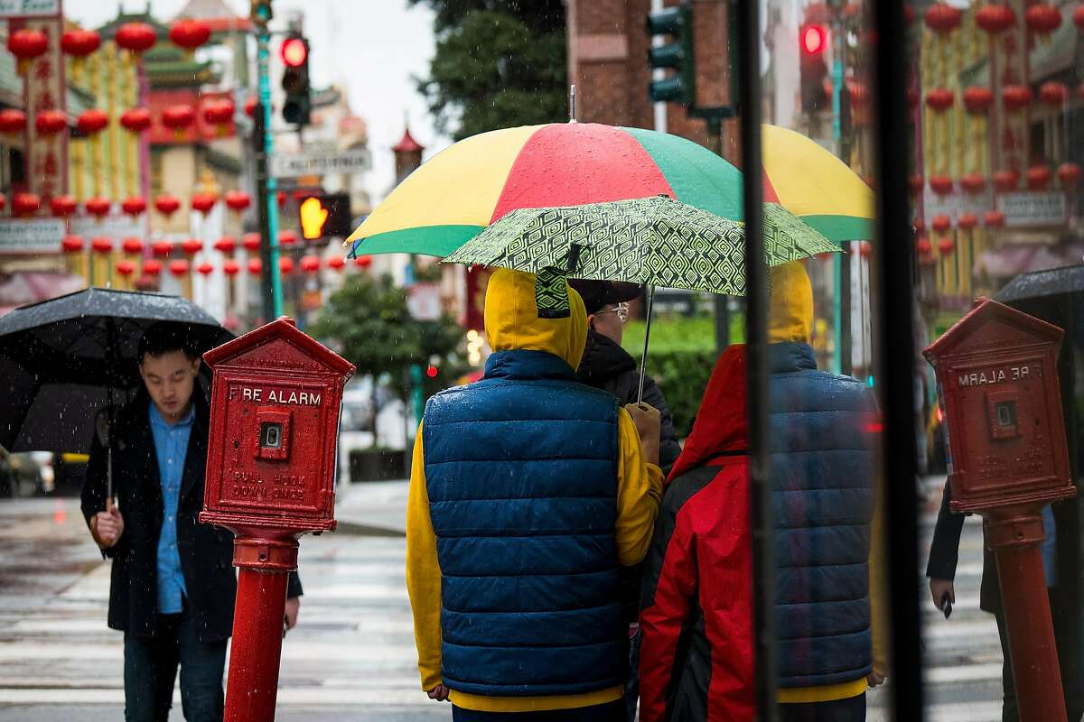 Pedestrians carry umbrellas while walking in the rain in downtown San Francisco, Calif. on Friday, Feb. 8, 2019.