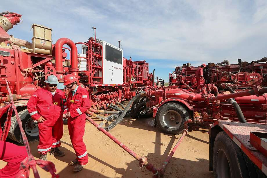 Halliburton employees work near rows of hydraulic fracturing pumping units at a three pad site Monday, June 26, 2017, in Midland.  CONTINUE to see recent earnings from area energy companies. Photo: Steve Gonzales, Houston Chronicle