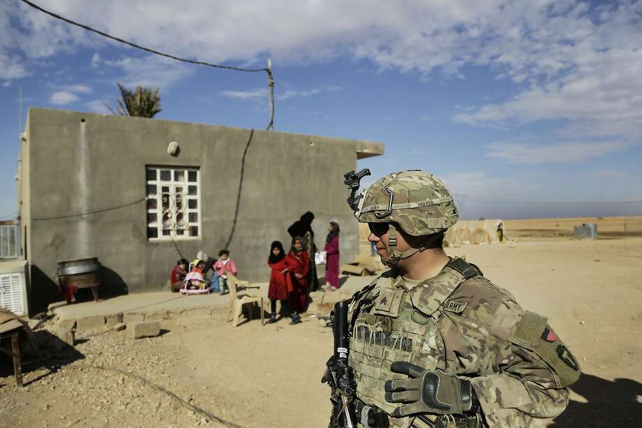 """FILE - In tU.S. Army soldiers speak to families in rural Anbar on a reconnaissance patrol near a coalition outpost in western Iraq. Iraq's president has slammed comments by U.S. President Donald Trump who he says he wants to keep U.S. troops in Iraq """"to watch Iran."""" Barham Salih said Monday, Feb. 4, 2019 that Trump did not ask Iraq's permission for American troops stationed there to watch Iran, describing his comments as """"strange.""""(AP Photo/Susannah George, File) Photo: (AP Photo/Susannah George, File)"""