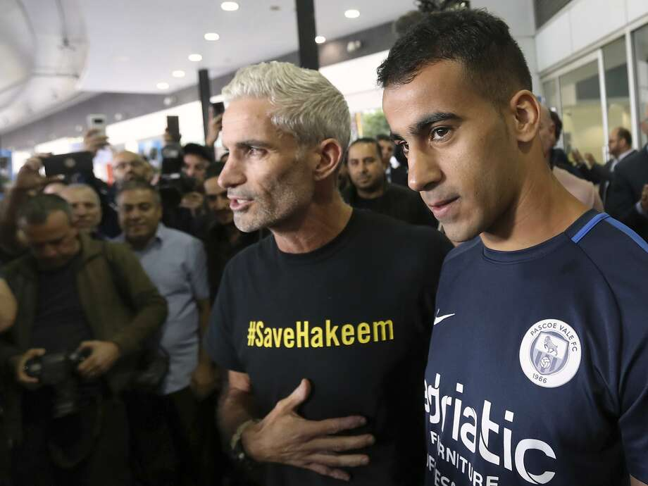Hakeem Al-Araibi (right) arrives in Melbourne, flanked by former Australia national team captain Craig Foster. Al-Araibi had feared being extradited from Thailand to Bahrain. Photo: David Crosling/Associated Press