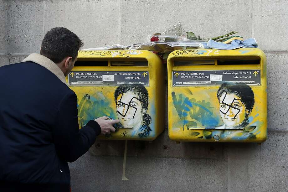 A French street artist cleans the vandalized mailboxes with swastikas covering the face of the late Holocaust survivor and politician Simone Veil, in Paris. Photo: Michel Euler/Associated Press