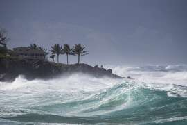 In this photo taken Feb. 10, 2019, rough surf hits Oahu's Waimea Bay near Haleiwa, Hawaii. A strong storm hit Hawaii and knocked out power, brought down tree branches, flooded coastal roads — and even brought snow. The National Weather Service said gusts hit nearly 70 mph (110 kph) in some areas. A high-surf advisory was in effect for north- and west-facing shores of several islands.