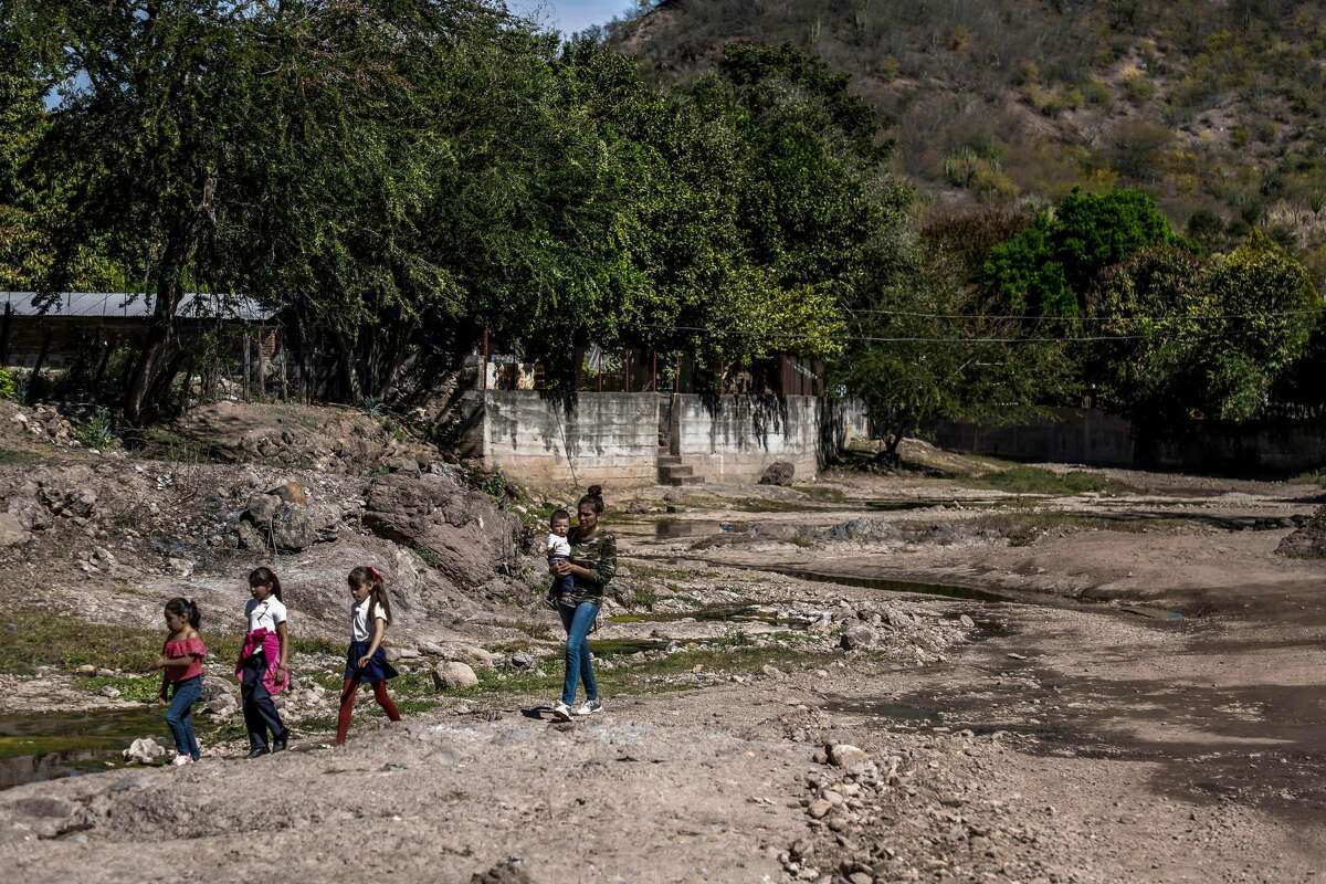"""People walk in Badiraguato -Mexican mobster Joaquin """"El Chapo"""" Guzman's hometown-, Sinaloa State, Mexico on February 8, 2019. - If """"El Chapo"""" returned to Badiraguato it would be a relief for its inhabitants because, according to them, there was neither poverty nor violence when he was there. Guzman was found guilty Tuesday by a New York jury of crimes spanning a quarter of a century as head of one of the world's most powerful drugs gangs."""