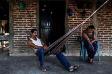 "Gonzalo Robles Quinonez (L) rests in a hammock in Badiraguato -Mexican mobster Joaquin ""El Chapo"" Guzman's hometown-, Sinaloa State, Mexico on February 8, 2019. - If ""El Chapo"" returned to Badiraguato it would be a relief for its inhabitants because, according to them, there was neither poverty nor violence when he was there. Guzman was found guilty Tuesday by a New York jury of crimes spanning a quarter of a century as head of one of the world's most powerful drugs gangs. (Photo by RASHIDE FRIAS / AFP)RASHIDE FRIAS/AFP/Getty Images"