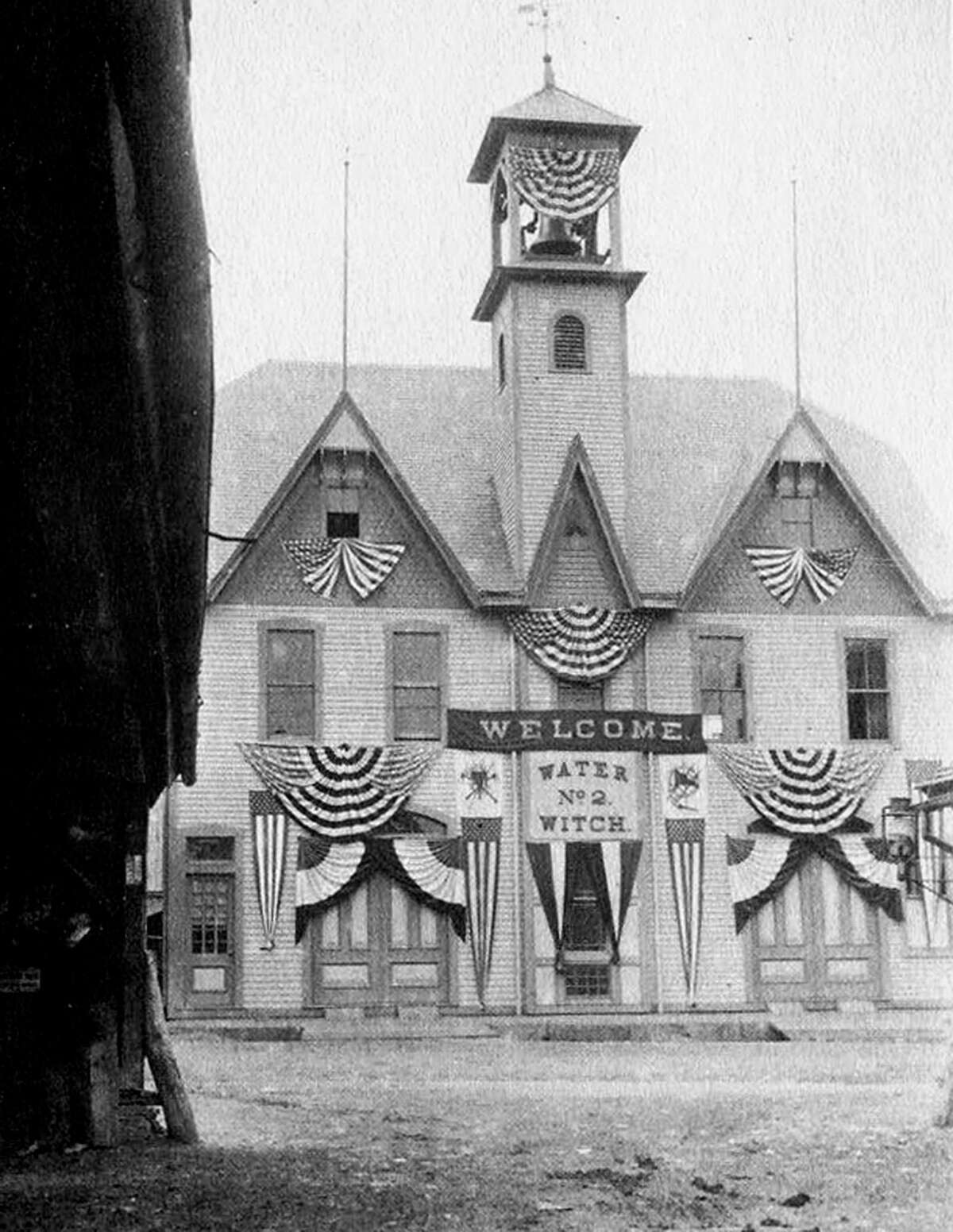 """The Water Witch Hose Co. No. 2 firehouse on Church Street in the village center of New Miford is all dressed up in 1900 for the traditional firemen's parade. Now home to Ruth Chase Flowers, the wooden edifice served as the town's chief fire station from the late 1800s until a state of the art, brick structure was built in 1960 on Route 67, alongside Great Brook, just south of the intersection of East and Bridge streets. If you have a """"Way Back When"""" photograph you'd like to share, contact Deborah Rose at drose@newstimes.com or 860-355-7324."""
