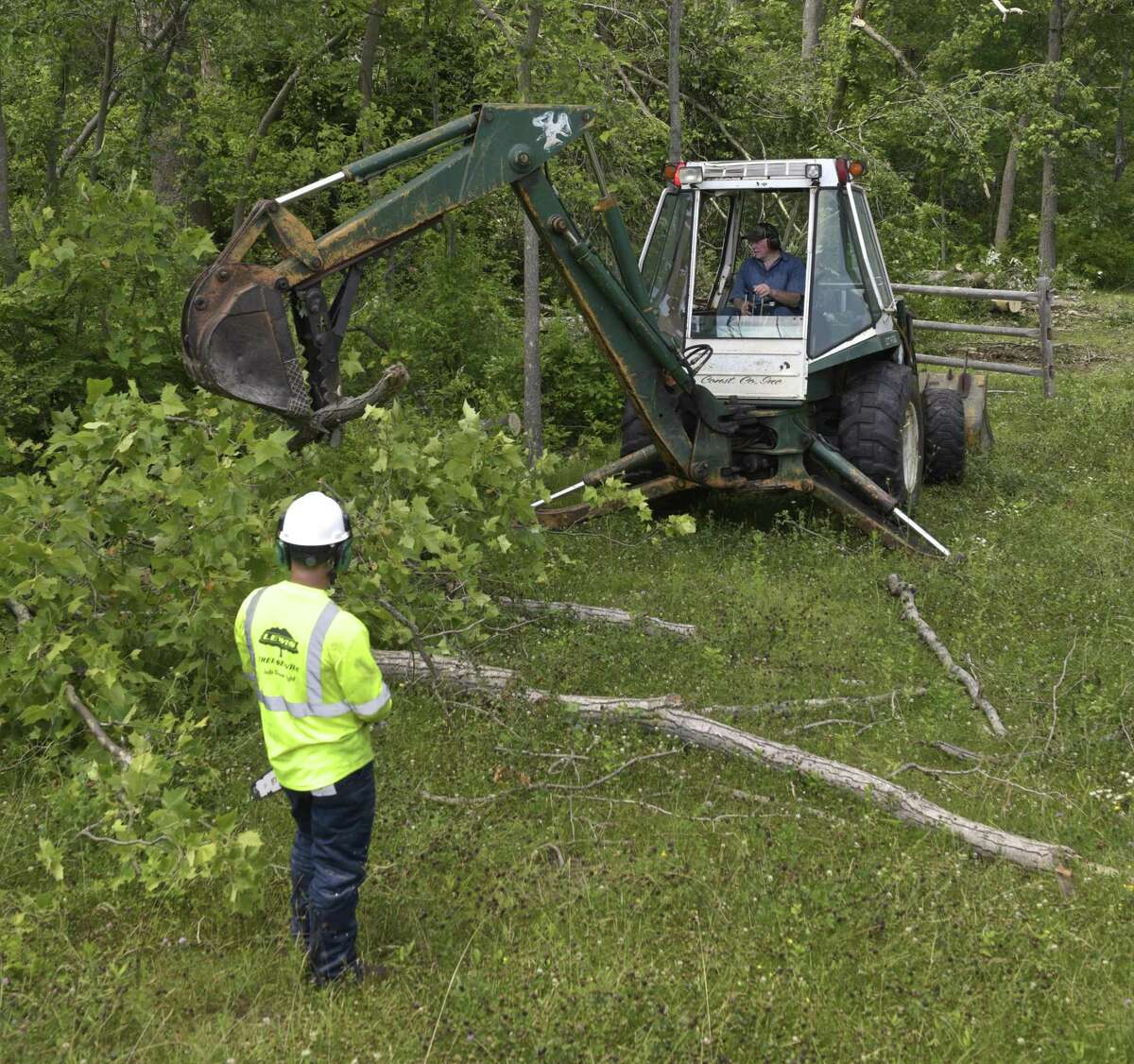Silman Pinedo, left, and Bud Wright work on cleaning up the Still River Greenway. The trail had been closed since the May 15 storm that injured two people on the trail. Lewis Tree Service and Wright Tree Service donated their time to clear the trail from the police station to downtown.