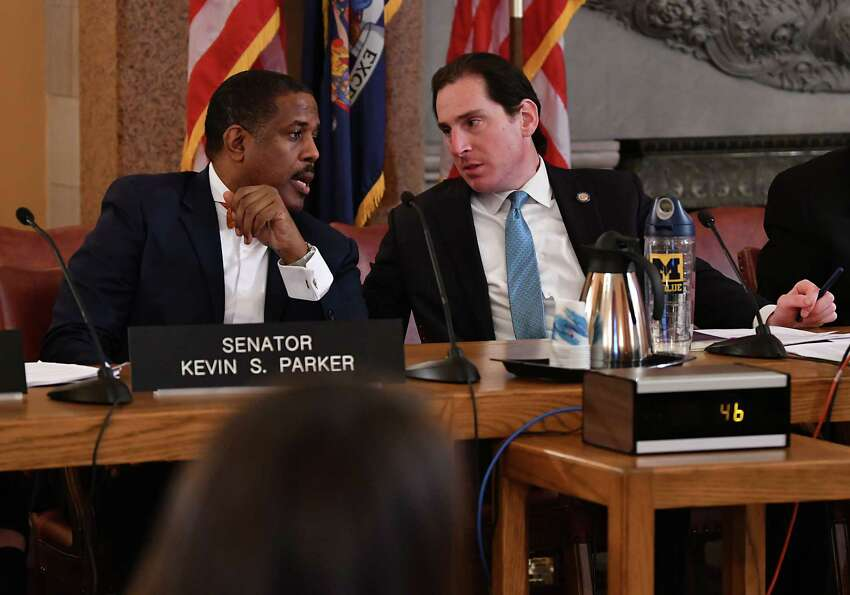 Senator Kevin Parker, left, talks with Senator Todd Kaminskyat, Chair of the Environmental Conservation Committee, during a public hearing on the Climate & Community Protection Act (?'CCPA?