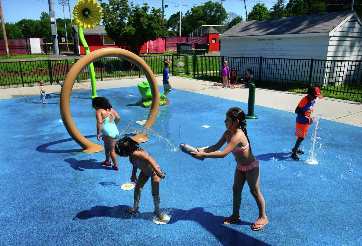 Jasmine Cabello, 8, of Stratford, throws water onto her little sister Nicole, 4, as they play at the spash pad at Longbrook Park in Stratford, Conn., on Tuesday July 10, 2018. The town is moving forward on putting another splash pad at Juliette Low Park.