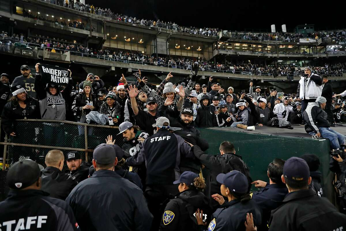Security personnel hold back Oakland Raiders' fans trying to storm the field after Raiders' 27-14 win over Denver Broncos during NFL game at Oakland Coliseum in Oakland, Calif. on Monday, December 24, 2018.