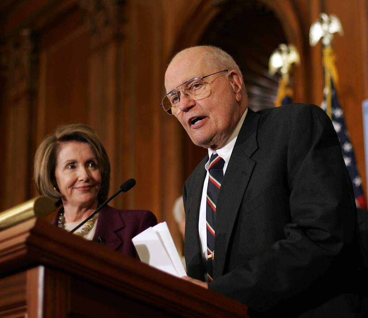 FILE - In this file photo taken on December 18, 2007 US Speaker of the House Nancy Pelosi (L) listens to remarks by Democratic Representative from Michigan John Dingell, Chairman of the House Energy and Commerce Committee, before signing the energy bill 18 December 2007 on Capitol Hill in Washington, DC. Trump took a shot at Dingell during a rally Wednesday, suggesting the deceased representative is in hell, prompting a response from Dingell's spouse.