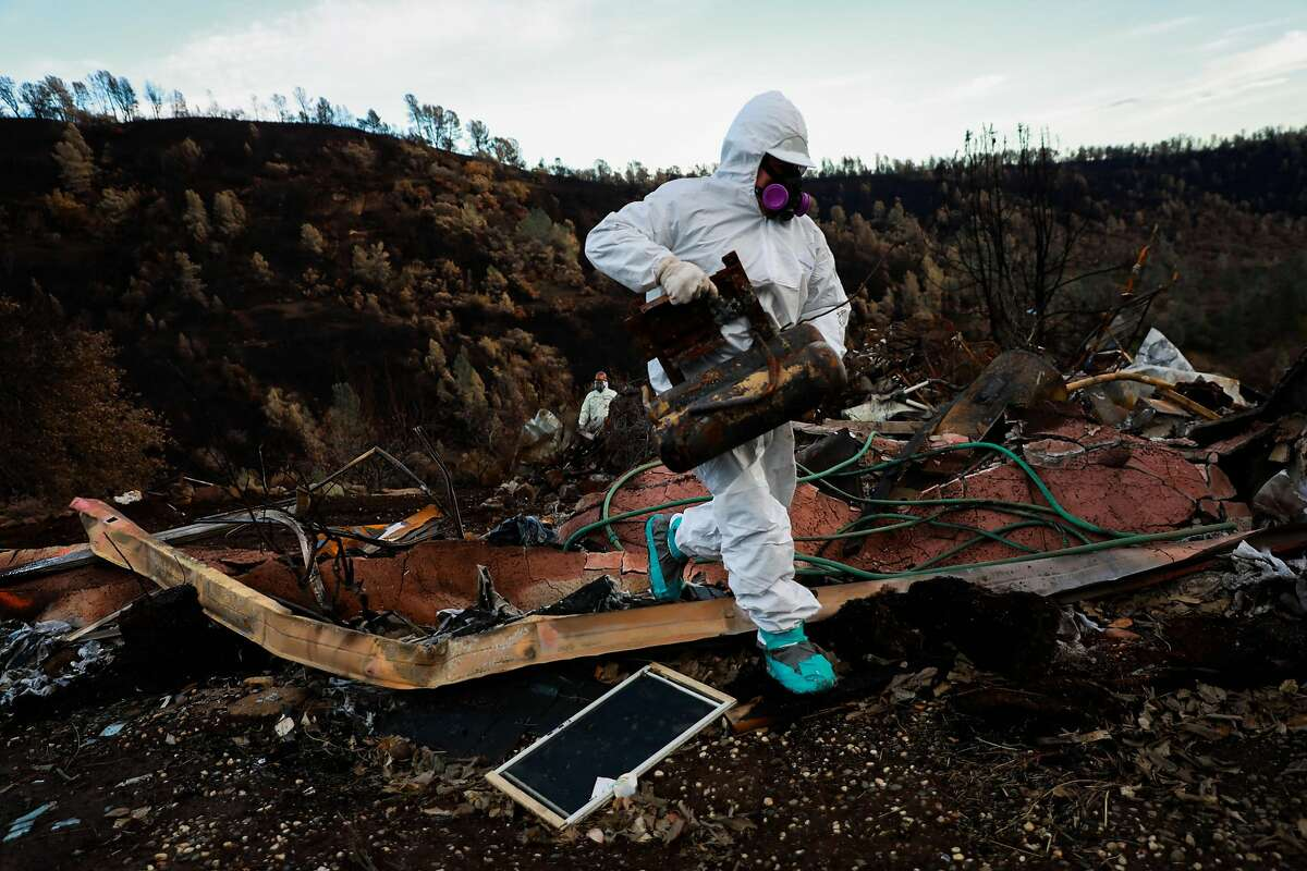 An EPA contractor carries metal material out of a property that was destroyed in the Camp Fire in Paradise, California, on Wednesday, Dec. 5, 2018.