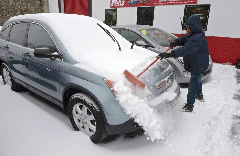 Javier Castillo clears the snow from a car at Feliz used cars during a snow storm in Danbury, Conn. Photo: H John Voorhees III, Hearst Connecticut Media / The News-Times