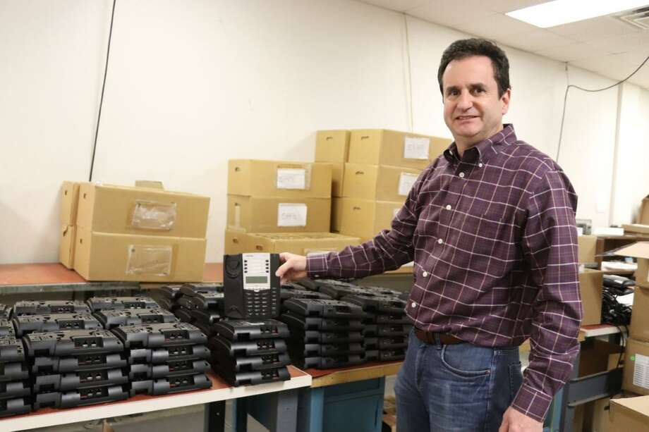 Fraser Ward, co-owner of ReWard Technologies, holds a refurbished phone console inside his company's facility at 101 North Plains Industrial Road in Wallingford. Photo: Contributed Photo