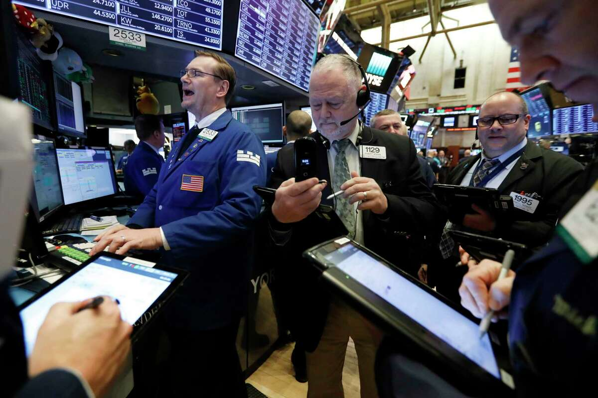 Specialist Patrick King, left, works with traders at his post on the floor of the New York Stock Exchange, Tuesday, Feb. 12, 2019. U.S. stocks are gaining in early trading after U.S. lawmakers reached a tentative deal to avoid another costly government shutdown. (AP Photo/Richard Drew)