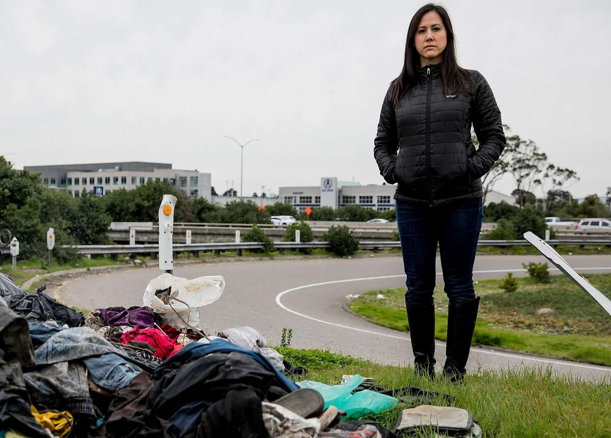 Save the Bay's Allison Chan poses for a portrait near a pile of illegally dumped trash gathered near the Coliseum Way on-ramp to Highway 880 in Oakland, Calif. Tuesday, Feb. 12, 2019.