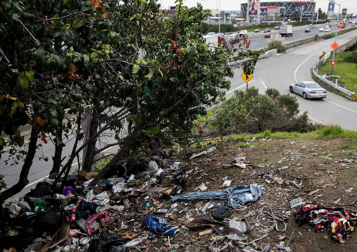 A pile of illegally dumped trash gathers around the overpass at Zhone Way along Highway 880 in Oakland, Calif. Tuesday, Feb. 12, 2019.