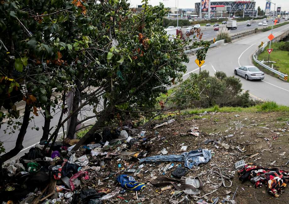 A pile of illegally dumped trash gathers around the overpass at Zhone Way along Highway 880 in Oakland, Calif. Tuesday, Feb. 12, 2019. Photo: Jessica Christian / The Chronicle