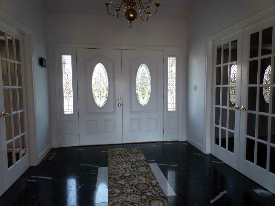 The marble foyer at 30 Ridgewood Court is adorned by stately French doors on either side that open to formal dining and living rooms. Photo: Coldwell Banker Residential Brokerage / ONLINE_CHECK