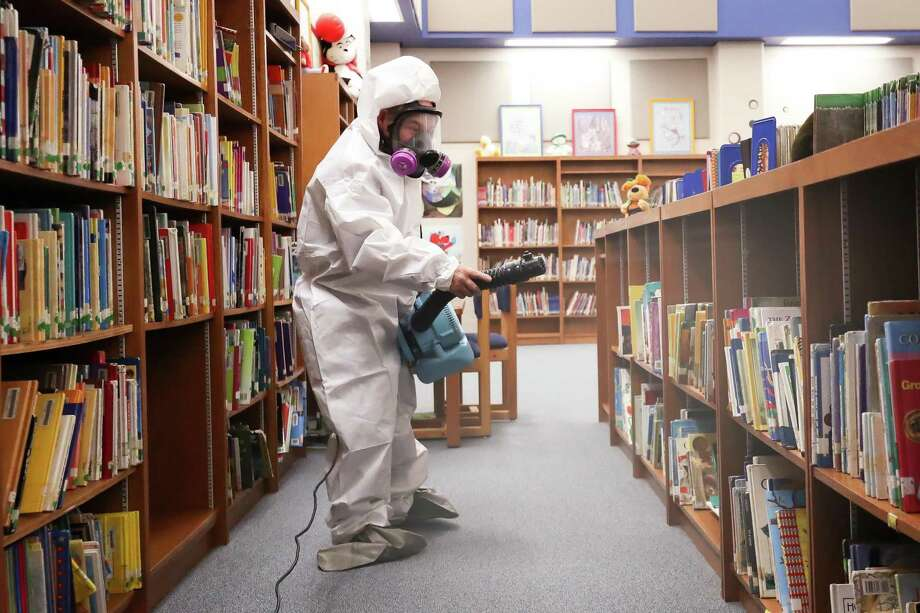 An employee for Aqua One sanitizes the Newton Elementary School's library on Tuesday. The cleaning was response to a school employee being diagnosed with meningitis. Photo provided by Heather Foster Photo: Heather Foster/Foster Photography / Foster Photography