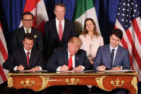 President Donald Trump, center, sits between Canada's Prime Minister Justin Trudeau, right, and Mexico's then-President Enrique Peña Nieto.