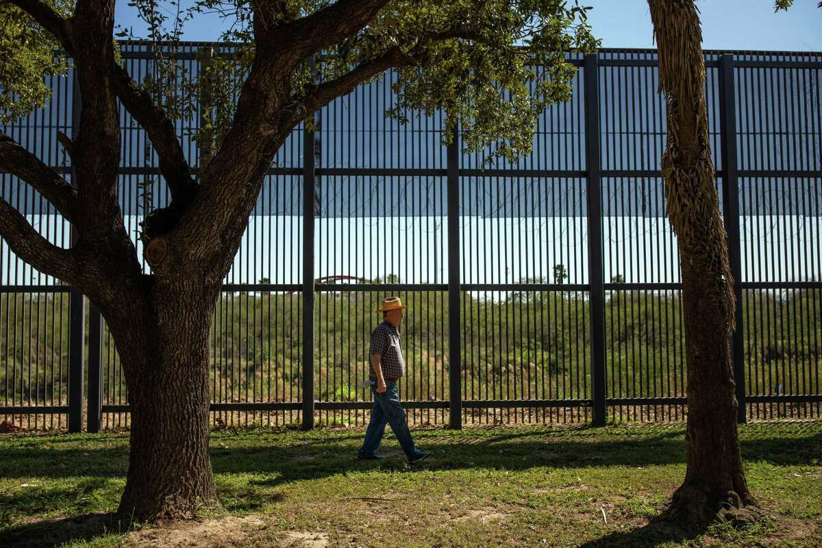 """A man walks along the border fence running through Alice Wilson Hope Park in Brownsville, Texas, on Jan. 20, 2019. If the White House and House Democrats are to reach a deal to avert another government shutdown by the Feb. 15, 2019 deadline, they must first reach a rough détente over what they are talking about - in particular, the definition of President Donald Trump's """"wall,"""" and of """"border security,"""" the Democrats' catchall description of their own approach."""
