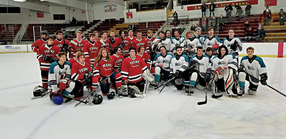 The Midland Feeny (in red) and Iron Range Miners (in white) hockey teams unite for a postgame photo at a tournament at Ferris State University in Big Rapids on Sunday, Jan. 27.