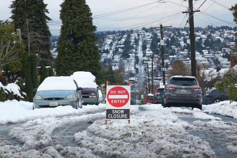 As snow begins to melt in Queen Anne, residents navigate the slushy roads and sidewalks, Feb. 12, 2019. Photo: Genna Martin, Seattlepi.com / SeattlePI