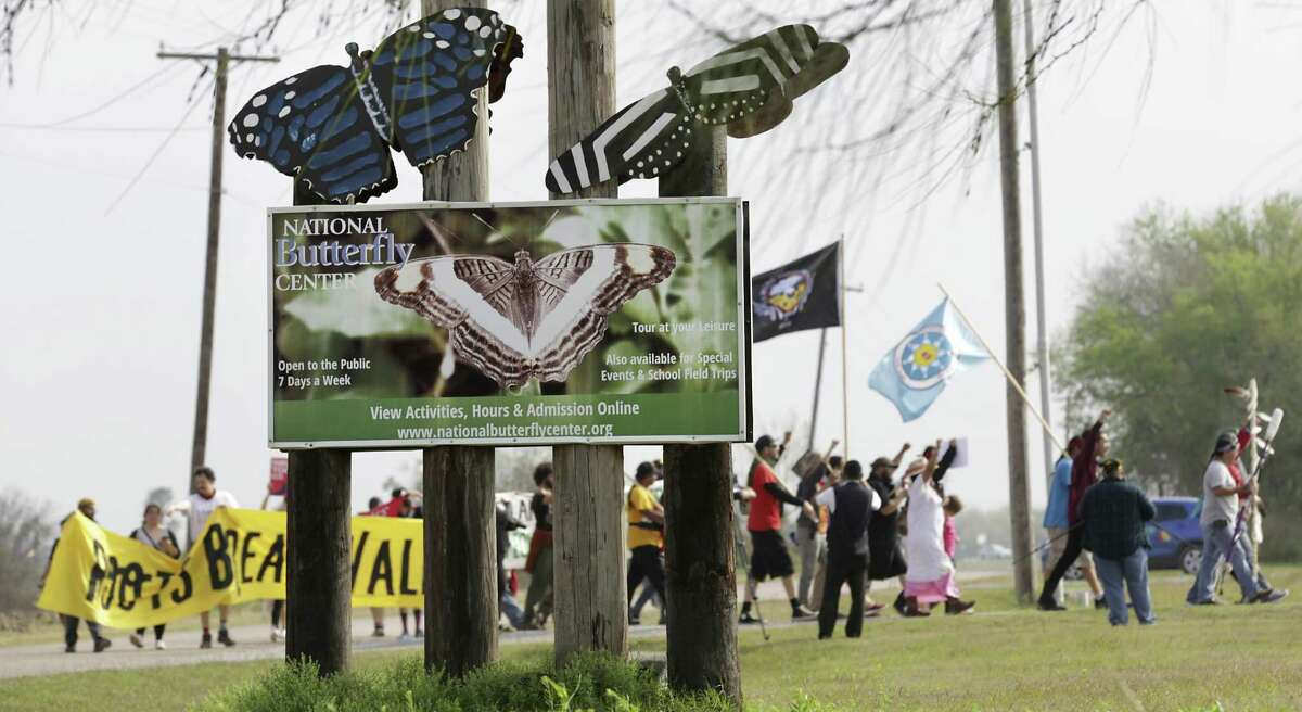 A group of Native Americans and supporters of the National Butterfly Center raise their fists in protest of the wall, as they enter the National Butterfly Center on Monday, Feb. 4, 2019.