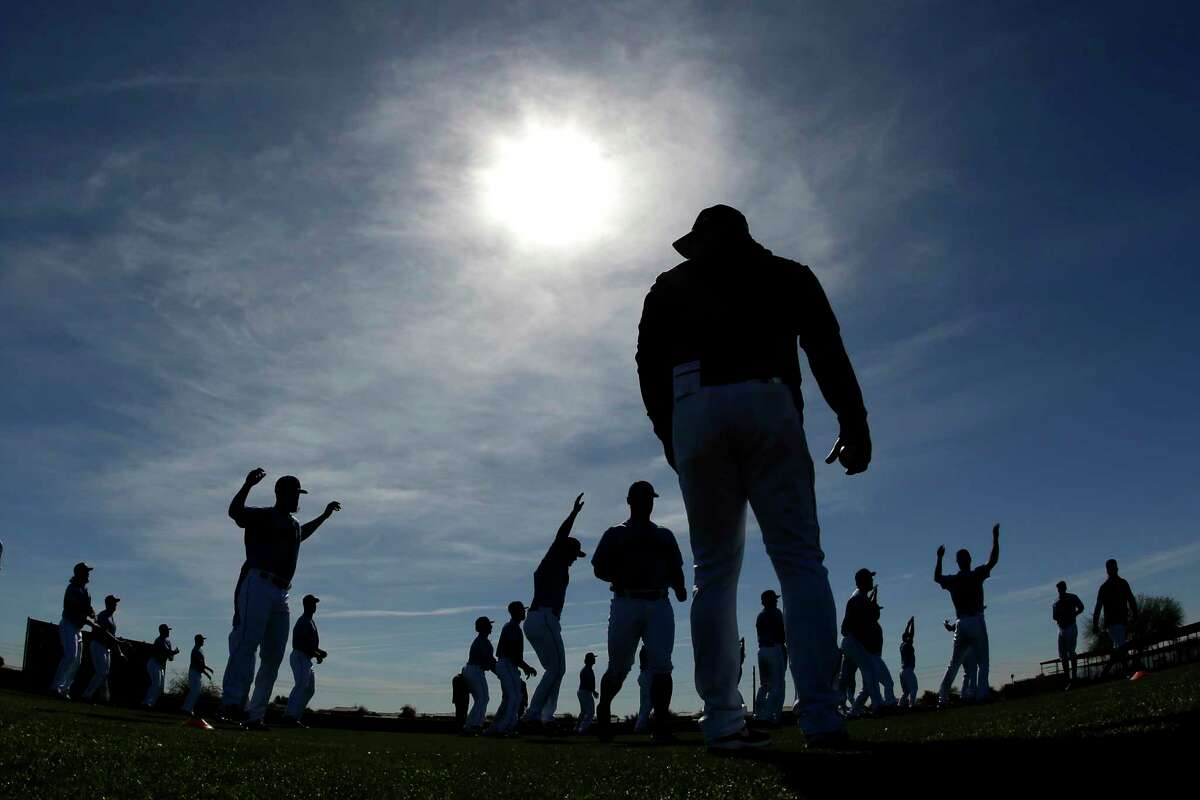 Players for the Seattle Mariners warm up during spring training baseball practice Tuesday, Feb. 12, 2019, in Peoria, Ariz. (AP Photo/Charlie Riedel)