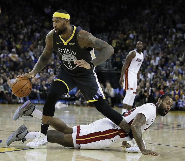 Golden State Warriors' DeMarcus Cousins (0) drives past Miami Heat forward James Johnson during the second half of an NBA basketball game, Sunday, Feb. 10, 2019, in Oakland, Calif. (AP Photo/Ben Margot)