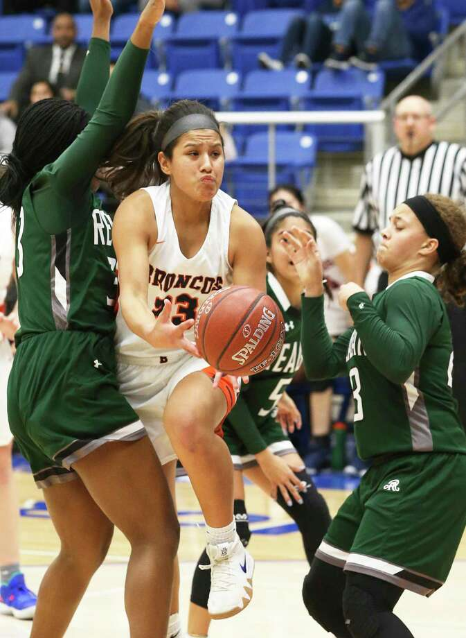 Broncos guard Arriana Villa squeezes through defenders in the lane as Brandeis plays Reagan in girls basketball playoff action at Northside Gym on February 12, 2019. Photo: Tom Reel, Staff / Staff Photographer / 2019 SAN ANTONIO EXPRESS-NEWS