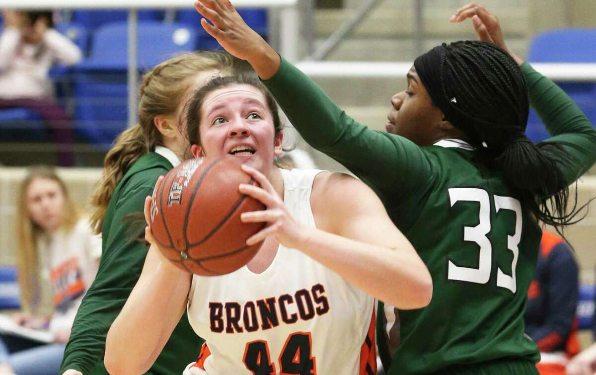 Sophia Haberer pivots around the Rattler's Olivia Iwuala as Brandeis plays Reagan in girls basketball playoff action at Northside Gym on February 12, 2019.