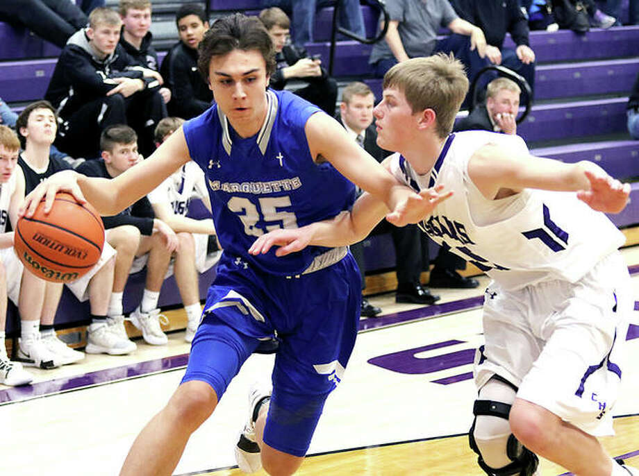 Marquette Catholic's Nate Hall (left) drves on Breese Central's Max Kampwerth Tuesday night in Breese. The Explorers beat the Cougars for the 25th win of the season. Photo: Greg Shashack | The Telegraph