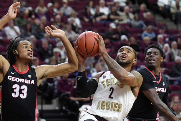 Texas A&M's TJ Starks (2) takes a shot between Georgia's Nicolas Claxton (33) and Teshaun Hightower (1) in the first half Tuesday, Feb. 12, 2019, at Reed Arena in College Station, Texas.