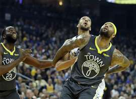 Golden State Warriors' DeMarcus Cousins and Draymond Green vie for rebound position against Utah Jazz' Rudy Gobert in 1st quarter during NBA game at Oracle Arena in Oakland, Calif., on Tuesday, February 12, 2019.
