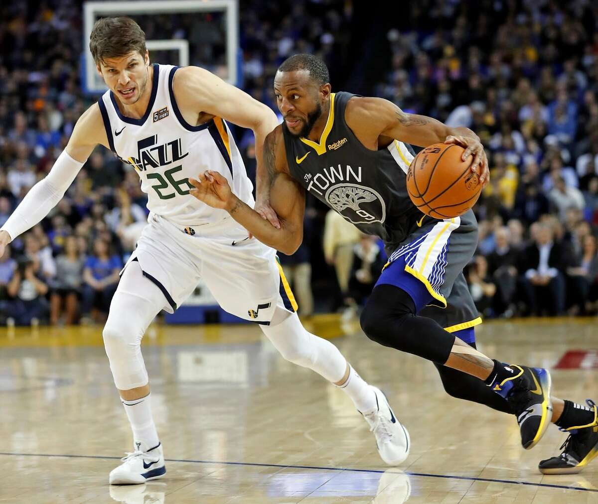 Golden State Warriors' Andre Iguodala drives against Utah Jazz' Kyle Korver during Warriors' 115-108 win in NBA game at Oracle Arena in Oakland, Calif., on Tuesday, February 12, 2019.