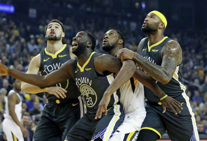 Warriors' Klay Thompson, Draymond Green and DeMarcus Cousins jockey for rebounding positions with Jazz's Derrick Favors in Golden State's win.