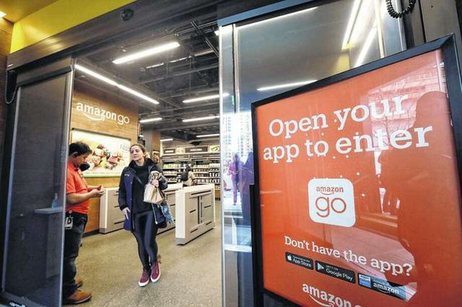 A shopper departs an Amazon Go store in January 2018 in Seattle. Get ready to say good riddance to the checkout line. A year after Amazon opened its first cashier-less store, startups and retailers are racing to get similar technology in other stores throughout the world, letting shoppers buy groceries without waiting in line. Photo: Elaine Thompson | Associated Press