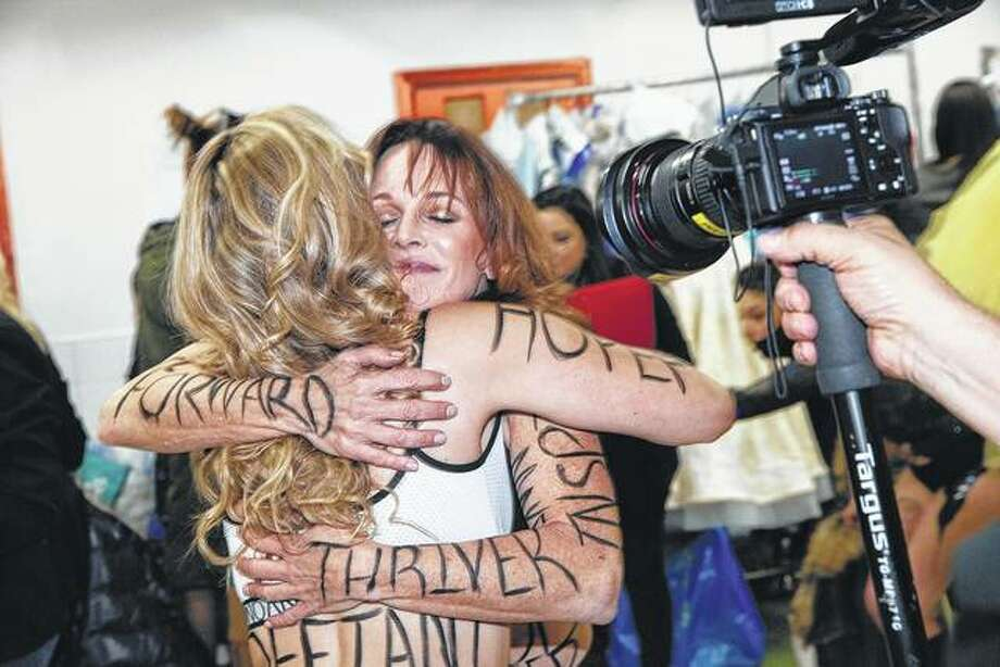 Susan Sullivan Danenberger hugs another woman Sunday at Fashion Week in New York. Both women were a part of a group of 24 who have or have had metastatic breast cancer.